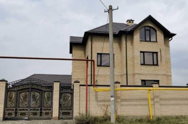Три этажа, светлый кирпич, кованые ворота с вензелями